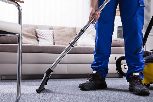 man vacuums the floor